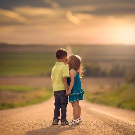 Фото Дети стоят на дороге взявшись за руки, девочка целует мальчика в щеку