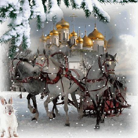 Фото Тройка белых лошадей, запряженных санями, мчится по дороге, на фоне красивого храма и ветки ели, идет снег