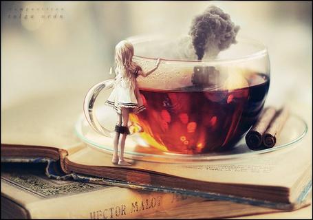 Фото Девочка стоит на стопке книг, и опираясь на стеклянную чашку чая, смотрит на идущий внутри чашки поезд, пускающий столб дыма, by ToLgaORDU
