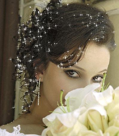 Фото Девушка брюнетка, с блеском на волосах и в глазах, прижимает к лицу букет из белых лилий