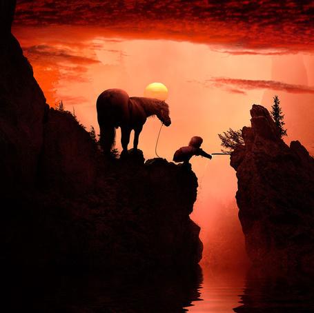 Фото Девочка, сидящая на корточках рядом с лошадью на горном утесе, пытается дотянуться рукой до тонкой струйки воды ручья, текущего через расщелину, автор Garas Ionut