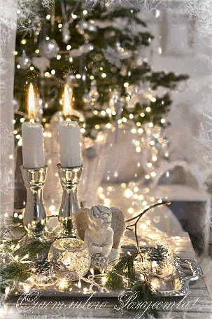 Фото На столе, на серебряном подносе, стоят две зажженные свечи, рядом фигурка ангела, лежат еловые шишки, на фоне наряженной елки (Счастливого Рождества!)