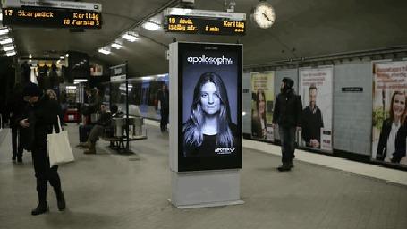 Фото Поезд в метро подходит к перрону, от сильного потока воздуха у девушки на рекламном щите развеваются волосы