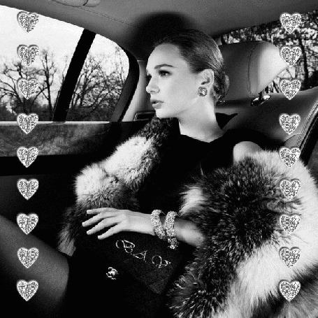 Фото Девушка сидит в автомобиле, на руке блестящий браслет, по бокам полоски из блестящих сердечек