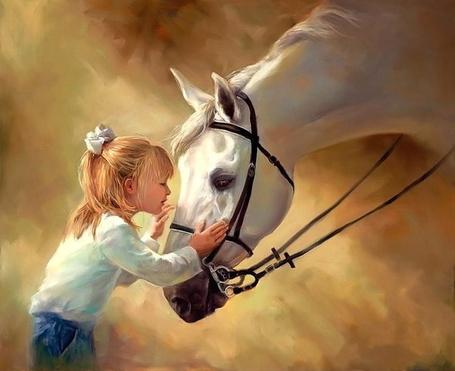 Фото Девочка в белой кофточке и джинсах, нежно держит ручками голову лошади