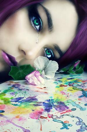 Фото Девушка с зелеными глазами, фиолетовыми волосами и губами склонила голову к листу бумаги с нарисованной абстракцией и лежащими на нем цветами, с глаза девушки стекает слеза