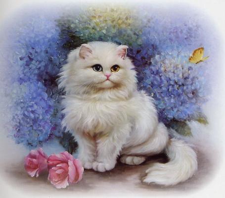 Фото Белая кошечка сидит рядом с цветами и смотрит на бабочку