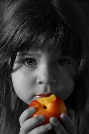 Фото Девочка кушает персик