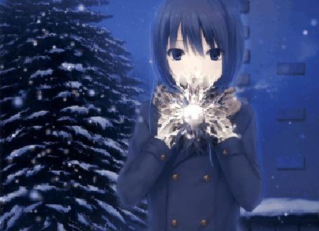 Фото Темноволосая девушка в черном пальто держит в руках снежинку