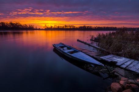 Фото Спортивная лодка, стоящая у деревянного причала берега озера на фоне заката на вечернем небосклоне с цветными облаками, автор Mariuszbrcz