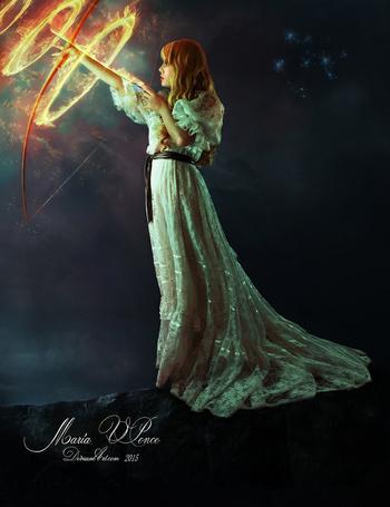 Фото Девушка в длинном платье с огненным луком и стрелой в руке