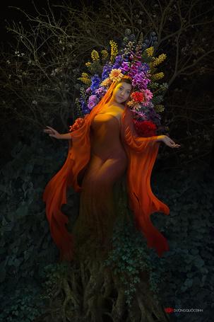 Фото Девушка азиатской внешности с короной из цветов на голове, стоящая на фоне кустов, автор DUONG QUOC DINH