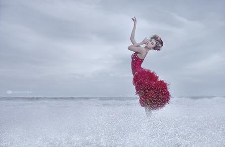 Фото Девушка азиатской внешности с венком из цветов на голове, стоящая в брызгах прибрежной, морской воды на фоне пасмурного неба, автор DUONG QUOC DINH