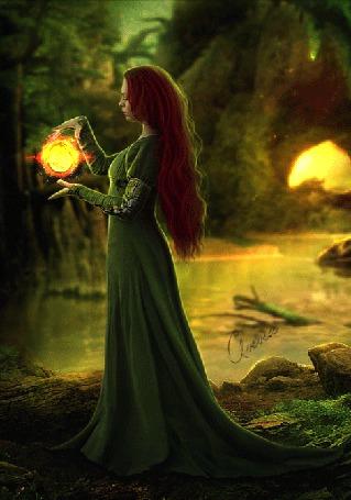 Фото Девушка в длинном зеленом платье с магическим шаром между ее рук стоит в лесу у водоема
