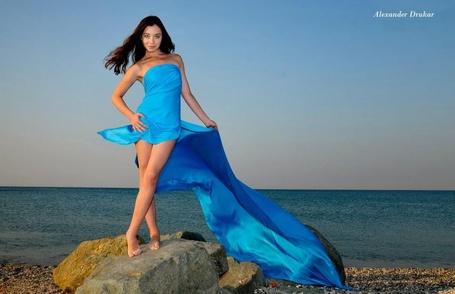 Фото Девушка в голубом платье с длинным шлейфом стоит на камне, лежащем недалеко от берега моря. Фотограф Александр Друкар
