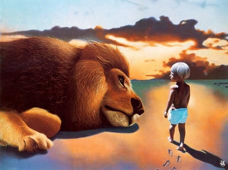 Фото Маленький мальчик стоит рядом со львом