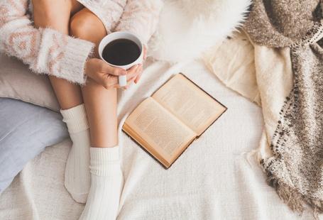 Фото Девушка с чашкой чая сидит на постели и читает книгу