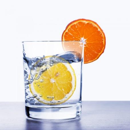 Фото Лимон в стакане с водой, на стакане насажена долька апельсина