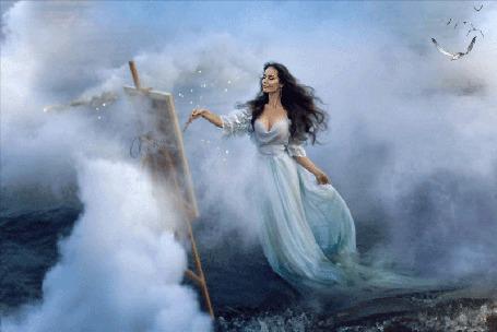 Фото Темноволосая, стройная женщина в длинном, белом платье, стоит у мольберта и рисует кистью, на берегу моря с клочьями тумана, поднимающимися от воды, вдалеке летят чайки