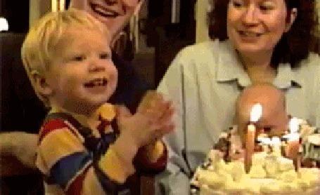 Фото Ребенок вместо того, чтобы задуть свечку на торте, пытается ее съесть