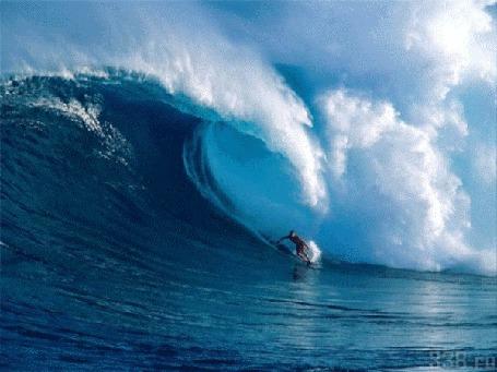 Фото Мужчина на доске для серфинга катится под гребень огромной волны