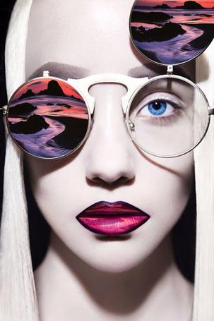 Фото Блондинка в очках, на губах и стеклах ее очков нарисованы элементы пейзажа