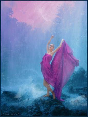 Фото Девушка в малиновом платье стоит на камне у моря, идет дождь