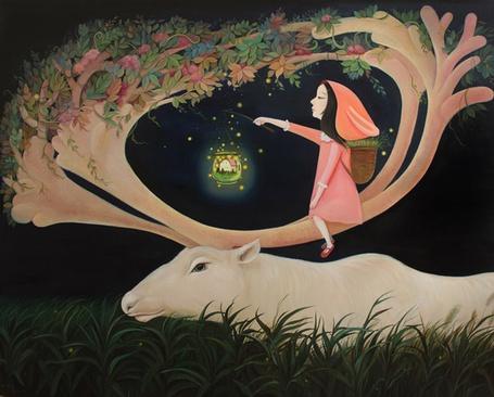 Фото Девочка сидит на рогах у оленя и держит в руке фонарик
