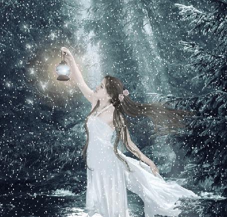 Фото Девушка в белом воздушном платье стоит в зимнем лесу и держит в руке зажженный фонарь