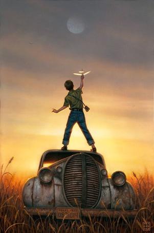 Фото Мальчик стоит на машине с самолетиком в руке