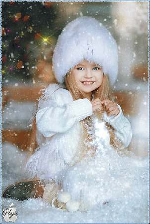 Фото Девочка в белой шапочке и курточке, с длинными русыми волосами, сидит недалеко от новогодней елки, идет снег