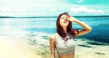 Фото Южнокорейская айдол-певица, участница группы Sistar, Сою / Soyu, одетая в серый топ, стоит под палящим солнцем, закрываясь от него рукой