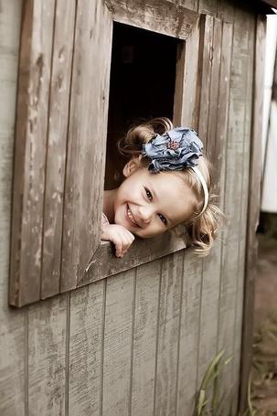 Фото Улыбающаяся девочка выглядывает из деревянного строения