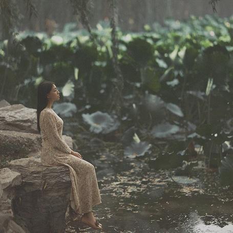 Фото Девушка с светлом платье сидит на камне возле водоема