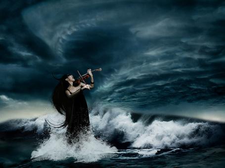 Фото Девушка эмоционально играет на скрипке, стоя в бушующем море