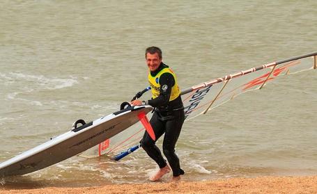 Фото Смеющийся мужчина выходит из моря на берег со своей доской и парусом после катания на волнах