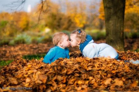 Фото Маленькая девочка целует маленького мальчика, сидя в сухой листве (KliDesign Art Photo)