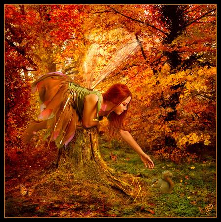 Фото Девушка эльф с крылышками за спиной, сидя на пенечке протянула руку к белке