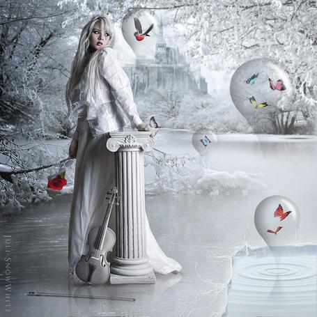 Фото Светловолосая девушка в длинном, белом платье со следами слез на лице, стоящая в воде невдалеке от берега озера, держащая в одной руке красную розу, другой рукой оперевшись о каменную колонну с прислоненной к ней скрипкой, лежавшим в воде смычком, со стоящими в разных местах стеклянными, грушевидными шарами с порхающими в них бабочкам и птицей, автор Juli-Show White