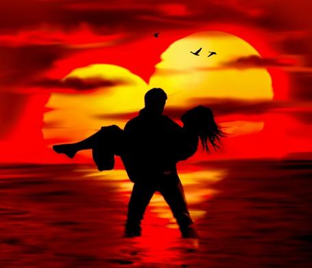 Фото Темный силуэт мужчины, стоящего в воде и держащего на руках девушку, на фоне вечернего неба с заходящим Солнцем в форме сердца