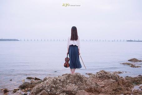 Фото Девушка, одетая в белую блузу и синюю юбку, стоит на камнях, держа в руках скрипку