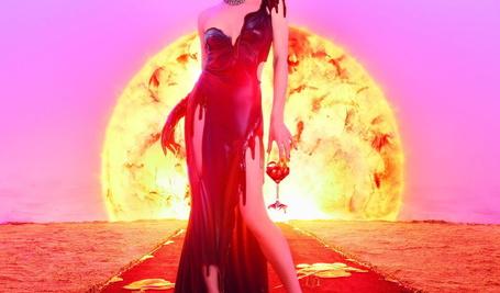 Фото Девушка на красной дорожке, в тающем на ней красном платье, с фужером красного вина, стоит на фоне огромного раскаленного Солнца