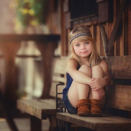 Фото Девочка с лентой волосах сидит на табурете, прижав руки к коленям