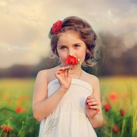 Фото Девочка с цветком в волосах нюхает цветок мака