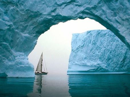 Фото Одинокая парусная яхта плывет среди ледяных айсбергов