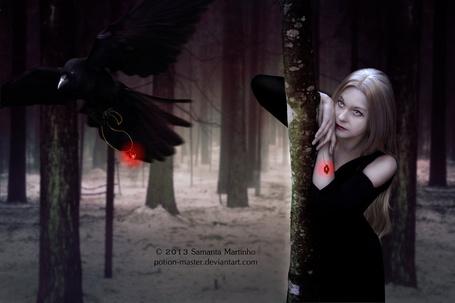 Фото Светловолосая девушка в черном платье, стоящая на заснеженной поляне, привалившись к дереву, с висящим у нее на руке на цепочке ярко горящим кулоном, наблюдает за черной вороной, летящей перед ней с таким же кулоном, автор Samanta Martinho