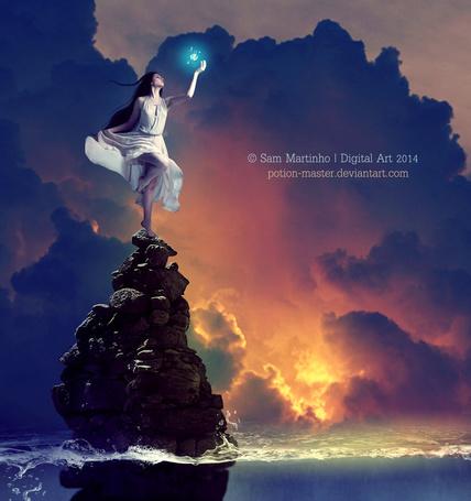 Фото Темноволосая, босоногая девушка в длинном, белом платье, стоящая на каменном утесе в море со светящимся синим цветом магическим шариком, парящим у нее над рукой на фоне заката на облачном небосклоне, автор Samanta Martinho