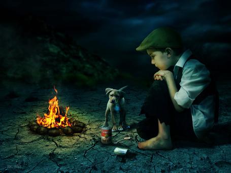 Фото Босоногий, бездомный мальчик, сидящий на потрескавшейся земле рядом с горящим костром, задумался каким образом ему открыть банку с консервами, рядом с ним стоит щенок на фоне ночного неба, автор rob has 1 left