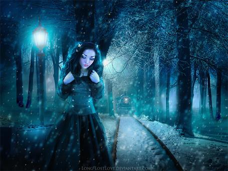 Фото Грустная, черноволосая девушка с безразличным взглядом, стоящая в свете горящего, уличного фонаря рядом с железнодорожными путями, занесенными снегом с приближающимся поездом, автор ChristabelleLAmort