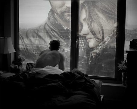 Фото Плюшевый мишка сиротливо сидит на подоконнике окна, в которое ранним утром смотрит парень сидя на постели, внизу просыпающийся город, в стекле отражение мужчины и женщины, разделенных черной рамой окна